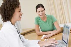 Docteur à l'aide de l'ordinateur portatif avec le femme dans le bureau du docteur Images stock