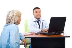 Docteur à l'aide de l'ordinateur portatif tandis qu'inverse avec le patient Image libre de droits