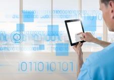 Docteur à l'aide du comprimé numérique avec l'interface bleue devant la fenêtre Image stock