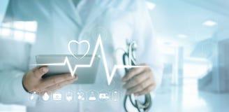 Docteur à l'aide du comprimé numérique avec le taux médical d'icône et de battement de coeur Photo libre de droits