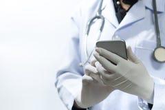 Docteur à l'aide du smartphone avec le patient dans la tache floue intérieure d'hôpital pour le fond, recherche image stock