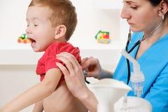 Docteur à l'aide du stéthoscope à examiner le petit garçon doux photos libres de droits