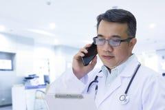 Docteur à l'aide du téléphone portable et regardant le disque de patient Images libres de droits