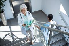 Docteur à l'aide du téléphone portable tout en marchant sur l'escalier Photographie stock libre de droits