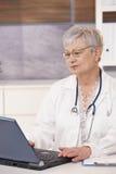 Docteur aîné à l'aide de l'ordinateur portatif Photos stock