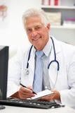 Docteur aîné au bureau prenant des notes Image libre de droits