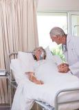 Docteur aîné avec son patient malade Photo libre de droits