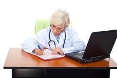 Docteur aîné occupé de femme à l'appareil de bureau Photo stock