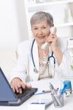 Docteur aîné parlant au téléphone Photo stock