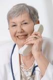 Docteur aîné parlant au téléphone Images stock