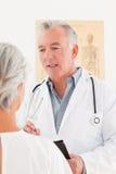 Docteur aîné parlant avec son patient malade Photographie stock libre de droits
