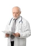 Docteur aîné regardant des papiers Photos libres de droits