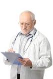 Docteur aîné regardant la planchette Images libres de droits