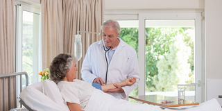 Docteur aîné retentissant son patient Photo stock