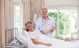 Docteur aîné retentissant son patient Photographie stock