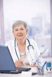 Docteur aîné travaillant au bureau Photographie stock