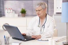 Docteur aîné travaillant au bureau Image libre de droits