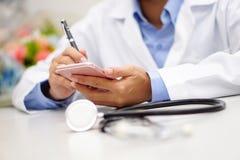 Docteur actif asiatique tenant le téléphone portable pour communiquer au sujet du travail à l'hôpital photographie stock
