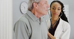 Docteur africain de femme écoutant la respiration patiente pluse âgé Photographie stock