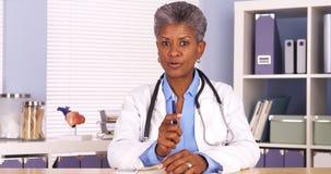 Docteur africain supérieur s'asseyant au bureau et parlant à l'appareil-photo photos stock