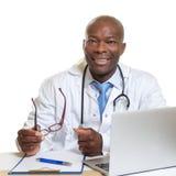 Docteur africain sur un bureau avec des verres dans sa main images stock
