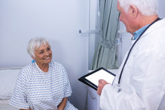 Docteur agissant l'un sur l'autre avec le patient supérieur dans la salle Photographie stock