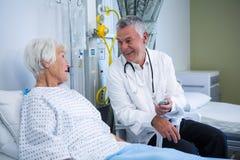 Docteur agissant l'un sur l'autre avec le patient supérieur dans la salle Images libres de droits