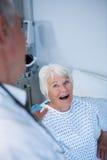 Docteur agissant l'un sur l'autre avec le patient supérieur dans la salle Images stock