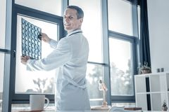 Docteur agréable satisfaisant tenant le balayage et le sourire de rayon X Images stock