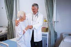 Docteur aidant le patient supérieur dans la salle Images stock