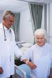 Docteur aidant le patient supérieur dans la salle Image libre de droits