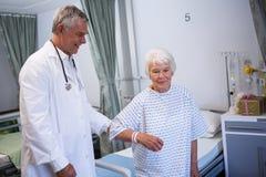 Docteur aidant le patient supérieur dans la salle Photographie stock libre de droits