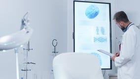 Docteur analysant des balayages de cerveau 3D sur le grand moniteur banque de vidéos
