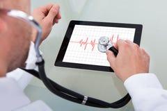 Docteur analysant le battement de coeur sur le comprimé numérique Photographie stock libre de droits