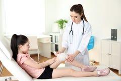 Docteur appliquant le bandage médical au genou blessé du petit patient images libres de droits