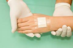 Docteur appliquant le plâtre en main images stock