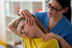 Docteur asiatique aux cheveux foncés précis étirant des muscles de cou images stock