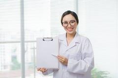 Docteur asiatique de femme se tenant avec le dossier à l'hôpital Images libres de droits