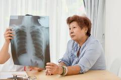Docteur asiatique et patient supérieur regardant le film radiographique ensemble Photographie stock