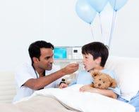 Docteur attentif donnant la médecine à un petit garçon photo stock