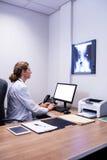 Docteur attentif travaillant sur l'ordinateur dans la clinique image stock