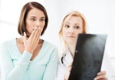 Docteur avec des patients regardant le rayon X Photographie stock libre de droits