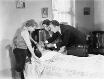 Docteur avec l'aide d'une mère et d'un frère essayant de donner à un enfant de malade la médecine (toutes les personnes représent Photographie stock