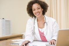 Docteur avec l'ordinateur portatif dans le bureau du docteur photographie stock libre de droits