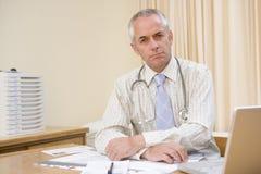 Docteur avec l'ordinateur portatif dans le bureau du docteur Photos libres de droits