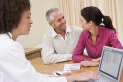 Docteur avec l'ordinateur portatif et les couples dans le bureau du docteur Photos stock