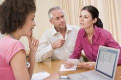 Docteur avec l'ordinateur portatif et les couples dans le bureau du docteur Images stock