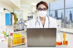 Docteur avec l'ordinateur portatif et les flacons regardant l'appareil-photo Photos libres de droits