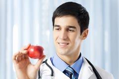 Docteur avec la pomme, au bureau images libres de droits