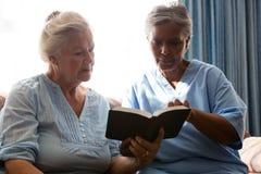 Docteur avec le livre de lecture supérieur de femme tout en se reposant dans la maison de retraite Photo libre de droits
